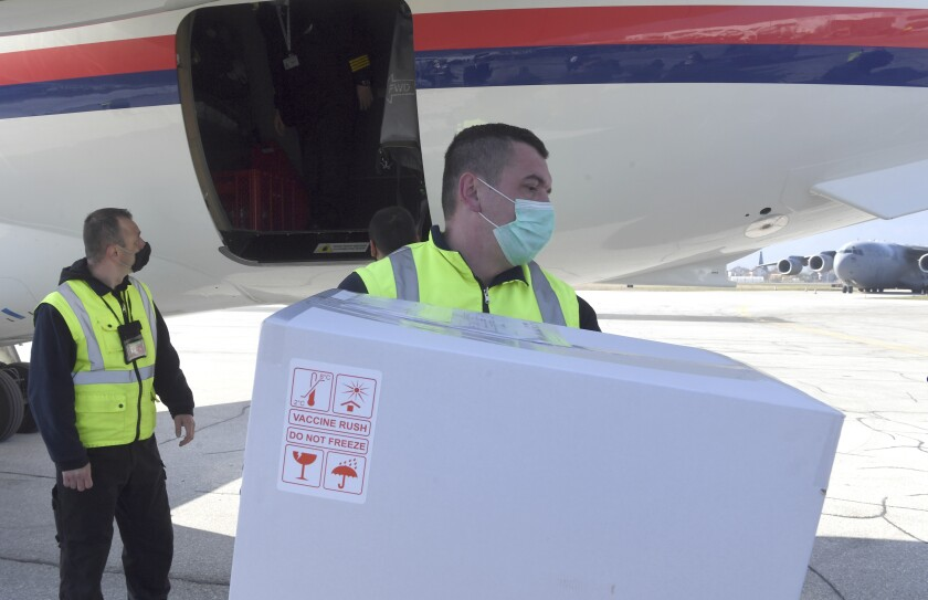 In this photo provided by the Serbian Presidential Press Service, a worker holds a box of the Astra-Zeneca vaccines at Sarajevo Airport, Bosnia, Tuesday, March 2. 2021. Bosnia on Tuesday received 10,000 vaccines from neighboring Serbia amid a dispute with the international COVAX mechanism over a delay in planned shipments. Serbia's populist President Aleksandar Vucic flew to the Bosnian capital of Sarajevo to deliver the Astra-Zeneca vaccines to the authorities there. (Serbian Presidential Press Service via AP)