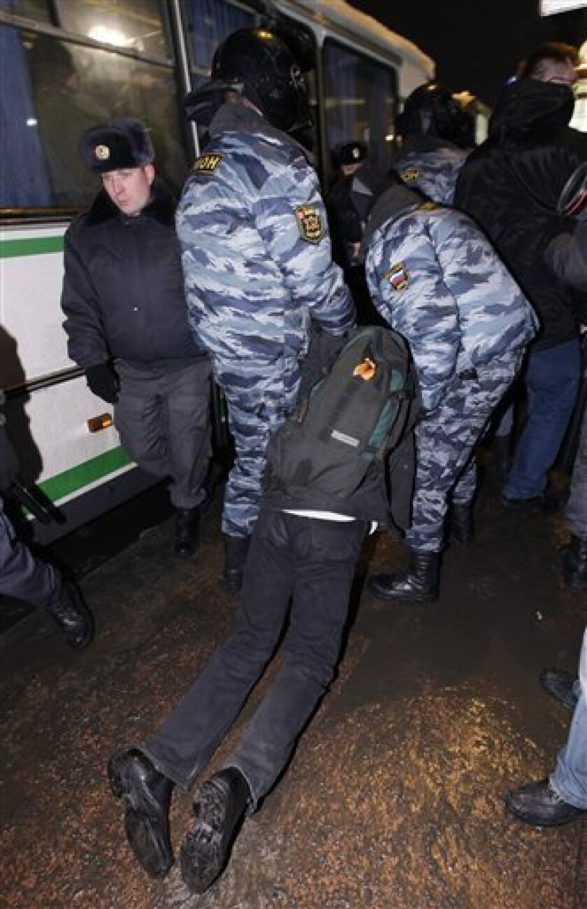 OMON, riot police, officers detain a participant of an unauthorized anti-Kremlin protest in St. Petersburg, Russia, Sunday, Jan. 31, 2010. Riot police quickly broke up the protest and detained several dozen demonstrators. The timing was a nod to the 31st Article of the Russian constitution, which guarantees the right of assembly.(AP Photo/Dmitry Lovetsky)