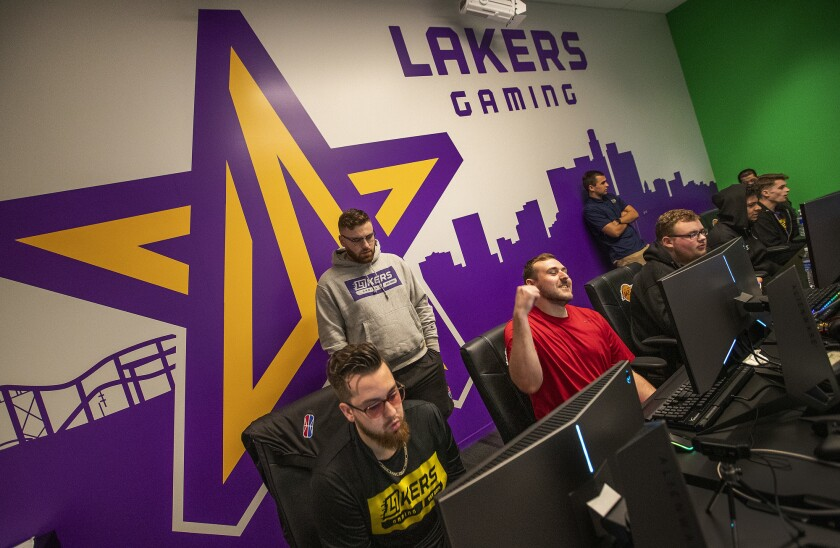 Lakers NBA 2K league players, seated from left, Mitchell Franklin, Christopher Doyle, Jordan Gates, Kevin Alvarado and Christopher Cantrell scrimmage last year against the Miami Heat 2K team.