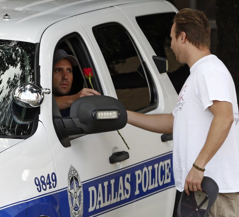 John Fife  hands a police officer guarding Jack Evans Police Headquarters a rose in Dallas on Friday July 8, 2016. Snipers opened fire on police officers in the heart of Dallas during protests over two recent fatal police shootings of black men.   (Nathan Hunsinger/The Dallas Morning News via AP)