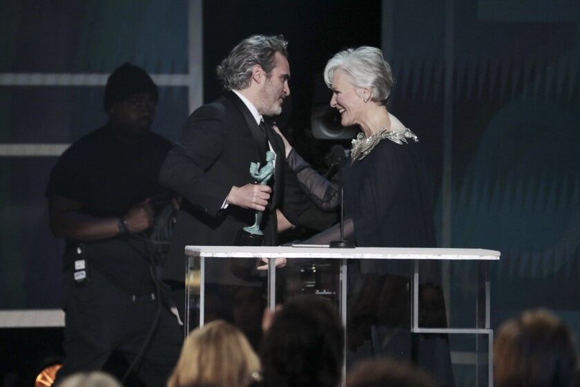 """""""Joker"""" star and SAG Awards winner Joaquin Phoenix accepts the lead actor prize from Glenn Close."""