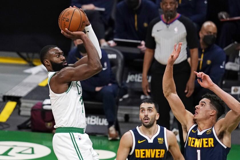 El base de los Celtics de Boston Jaylen Brown lanza el balón sobre el alero Michael Porter Jr.