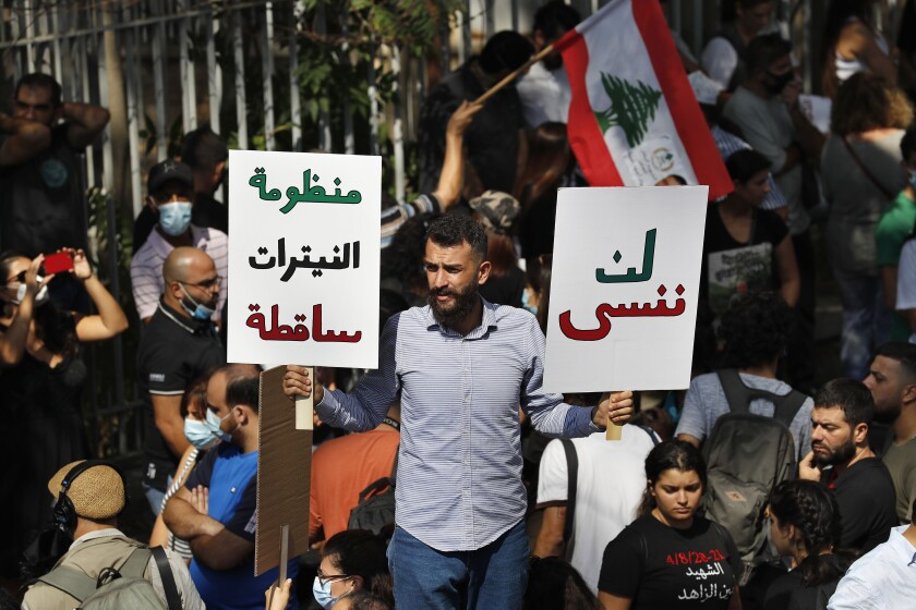 """A protester holds Arabic placards that reads: """"Will not forget, right, down with the system of nitrates,"""" outside a court building during a demonstration of solidarity with Judge Tarek Bitar who is investigating last year's deadly seaport blast, in Beirut, Lebanon, Wednesday, Sept. 29, 2021. Hundreds of Lebanese, including families of the Beirut port explosion victims, rallied Wednesday outside the court of justice in support of Bitar after he was forced to suspend his work. Bitar is the second judge to take on the complicated investigation. (AP Photo/Hussein Malla)"""