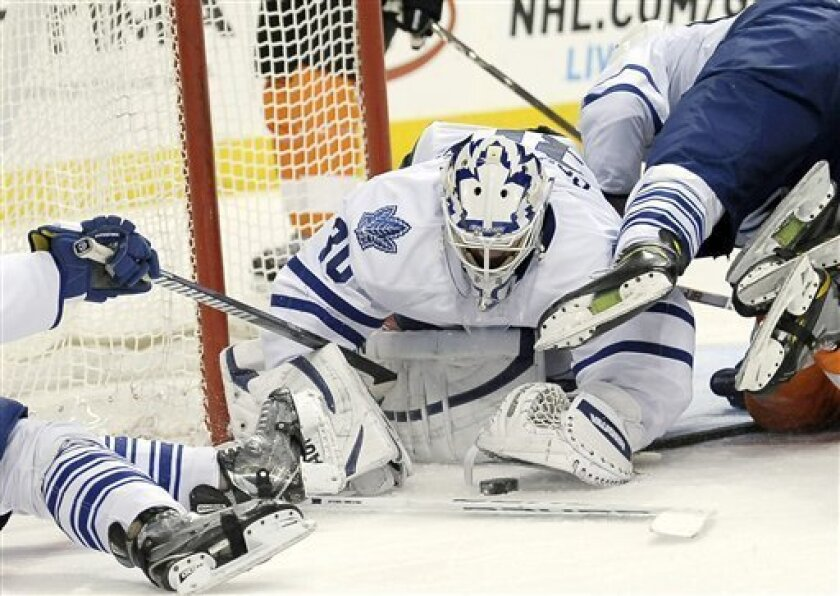 Toronto Maple Leafs' Ben Scrivens (30) dives on a loose puck in front of the goal in the second period of an NHL hockey game against the Philadelphia Flyers on Monday, Feb 25, 2013, in Philadelphia. (AP Photo/Michael Perez)