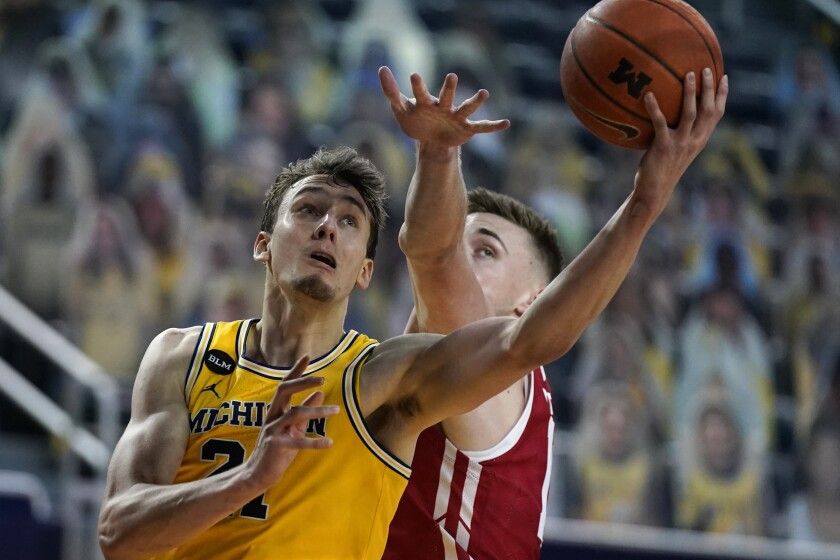 Michigan guard Franz Wagner makes a layup as Wisconsin forward Micah Potter defends.