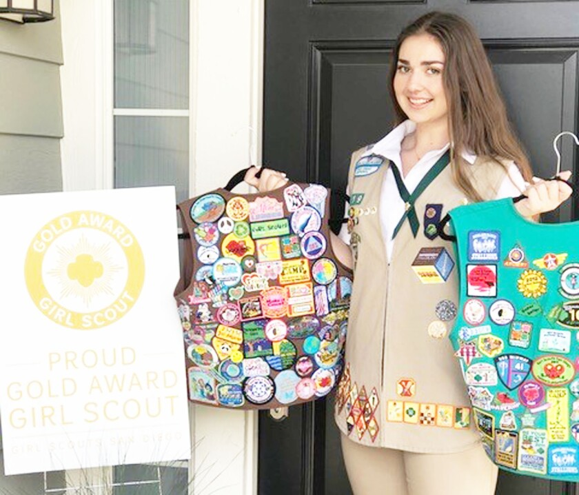 Gold Award Girl Scout Annalisa Simonetti holding her Brownie and Junior Girl Scout vests.