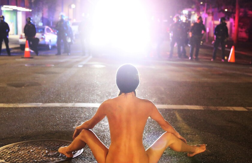 "A woman who has come to be known as ""Naked Athena"" confronts militarized federal agents in Portland, Ore., on July 18."