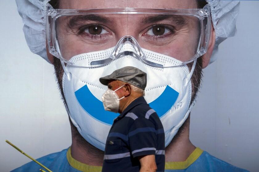 Un hombre camina frente a un cartel publicitario para una clínica en Barcelona