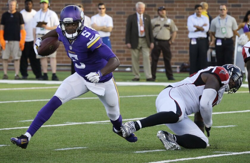 Minnesota Vikings quarterback Teddy Bridgewater gets kicked in the ankle as he runs from Atlanta Falcons defensive end Jonathan Babineaux during the second half of an NFL football game, Sunday, Sept. 28, 2014, in Minneapolis. Bridgewater was injured on the play. The Vikings won 41-28. (AP Photo/Ann Heisenfelt)