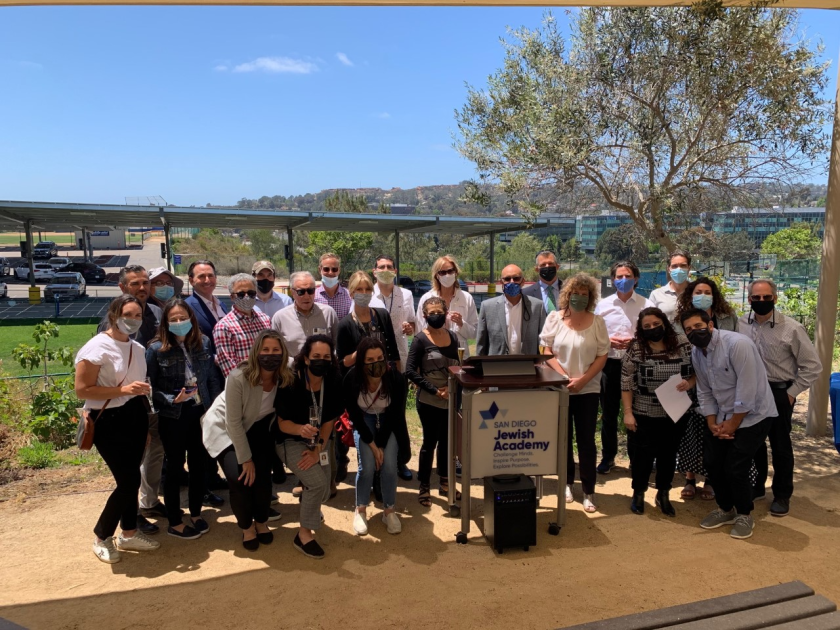 SDJA leadership and community members celebrate the activation of their solar project.