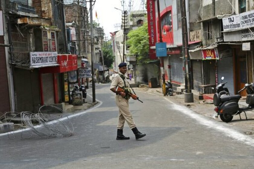 An Indian paramilitary soldier stands guard near closed shops in Jammu, in India's Kashmir region.  India has cracked down on the  region, revoking its quasi-autonomous status.