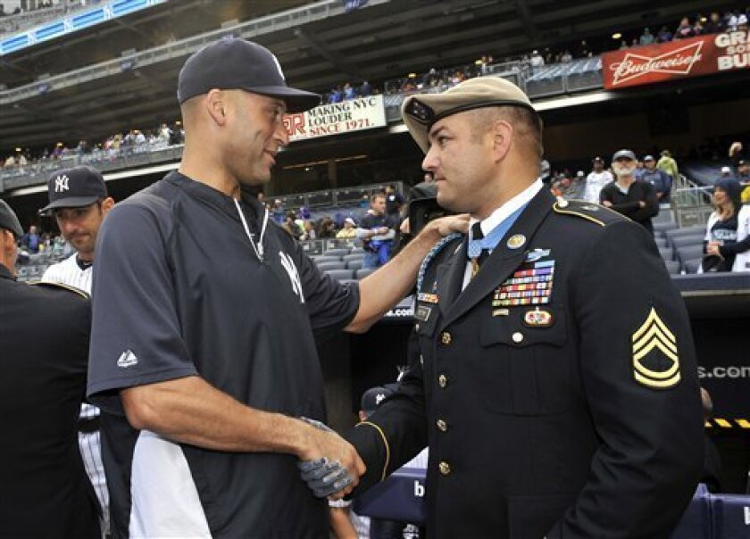 New York Yankees' Derek Jeter, left, shakes hands with Congressional Medal of Honor awardee Sgt. 1st Class Leroy Petry during ceremonies to honor the 10-year anniversary of September 11, 2001, before the baseball game between the Yankees and the Baltimore Orioles on Wednesday, Sept. 7, 2011, at Yankee Stadium in New York. (AP Photo/Kathy Kmonicek)