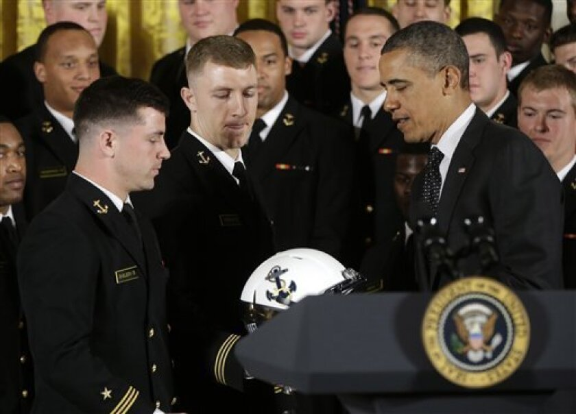 President Barack Obama is given a Navy football team helmet by players Bo Snelson, left, and Brye French, center, after presenting the Commander-in-Chief Trophy to the United States Naval Academy football team in the East Room of the White House in Washington, Friday, April 12, 2013. (AP Photo/Pabl