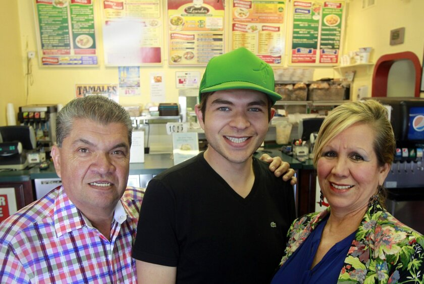 Members of the Parra family (from left) Hector Parra (father), Alex Parra (son), Lourdes Parra (mother) stand in their restaurant called Lourdes Mexican Food on Friday in Escondido, California.