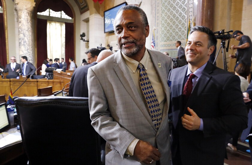 City Councilman Curren D. Price, left, celebrates with fellow Councilman Joe Buscaino, as the council backed a proposed law that Los Angeles workers would be able to earn at least six paid sick days annually.