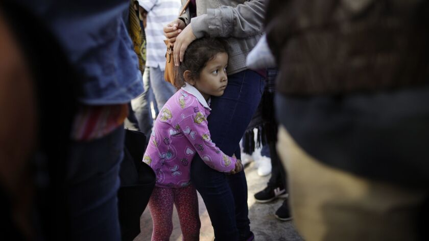 Nicole Hernandez holds on to her mother on June 13 as they wait with other families to request political asylum in the United States, across the border in Tijuana, Mexico.