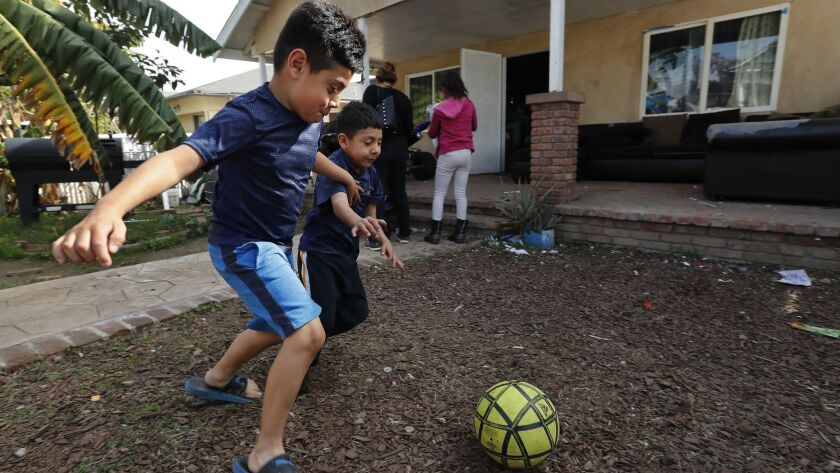 BOYLE HEIGHTS, CA-MARCH 19, 2018: Axel Vasquez, 7, left, and his brother Neymar, 5, play in the fro