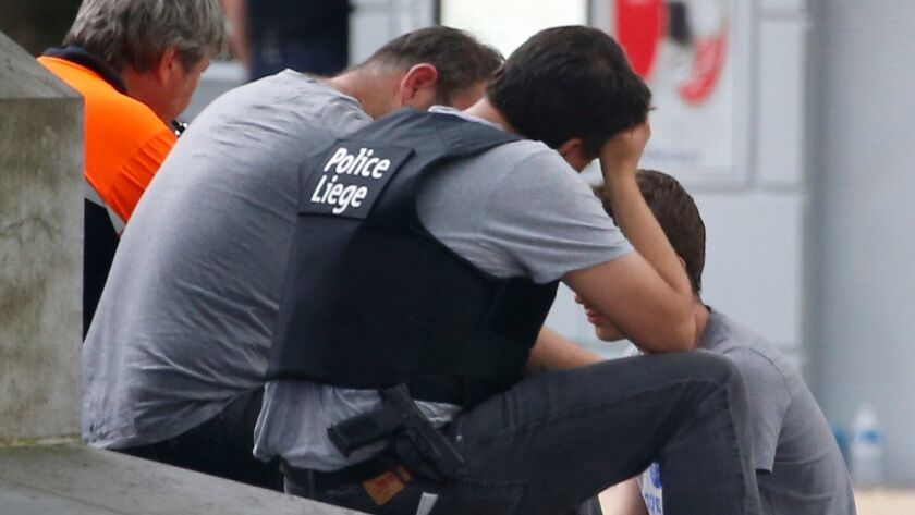 A man is comforted by officials at the scene following a shooting in Liege, Belgium, on May 29.