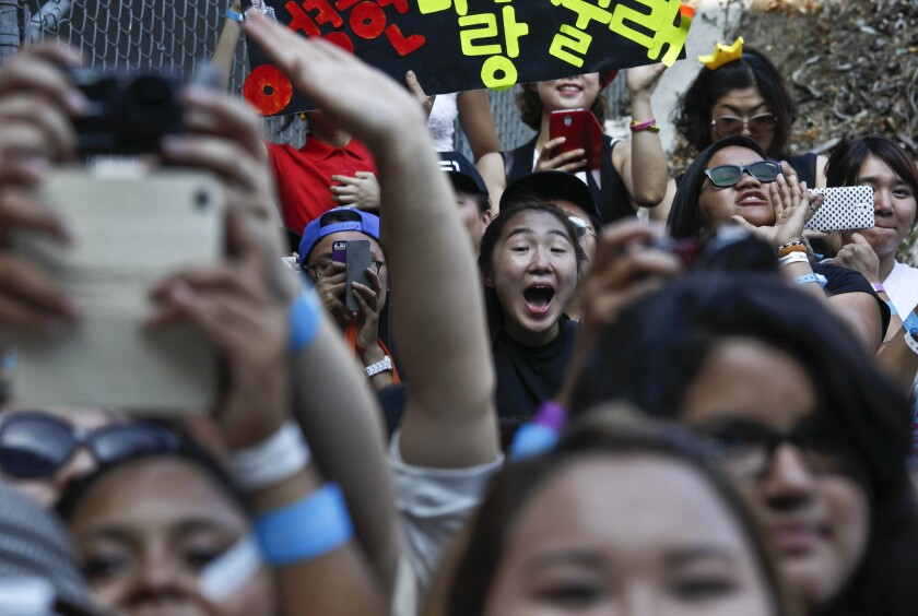 Fans scramble to get photographs of K-pop supergroups during a meet-and-greet before a concert at the Los Angeles Sports Arena.