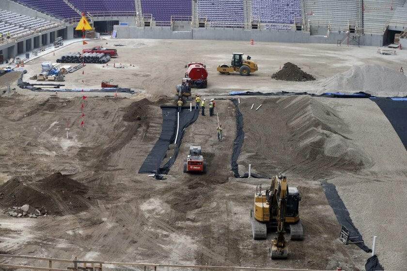 Construction workers prep the field for asphalt during a media tour, Tuesday, Feb. 16, 2016, of the new U.S. Bank stadium in Minneapolis which will be home to the Minnesota Vikings NFL football team.  (AP Photo/Jim Mone)