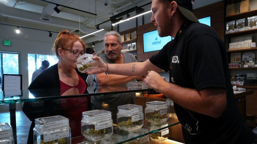 Michael Gladen and his wife Donna are assisted by budtender Jay Frentsos at Urbn Leaf with selecting from one of the many varieties of marijuana.