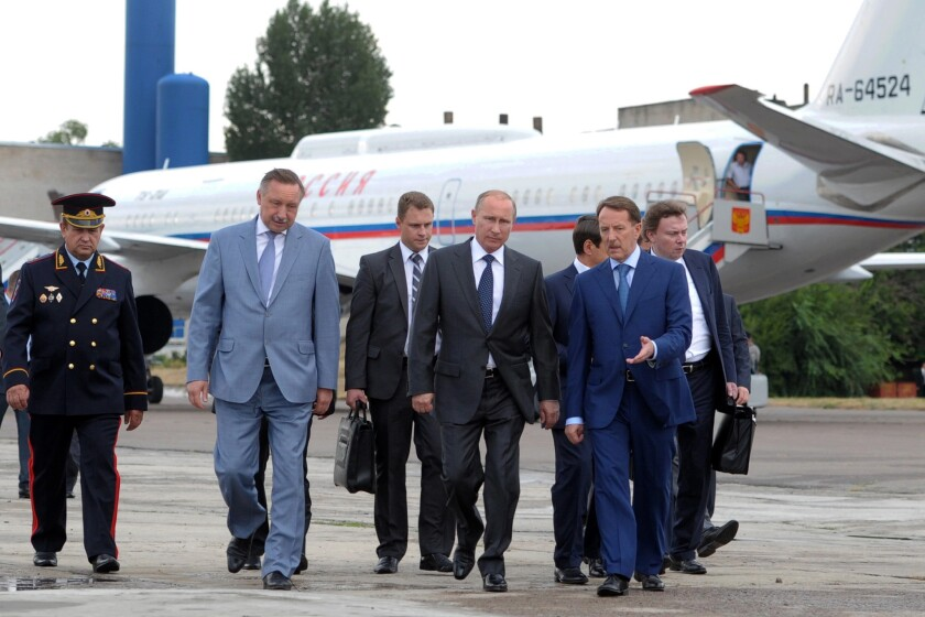 Russian President Vladimir Putin, foreground center, walks surrounded by officials upon his arrival in Voronezh, Russia, on Tuesday.