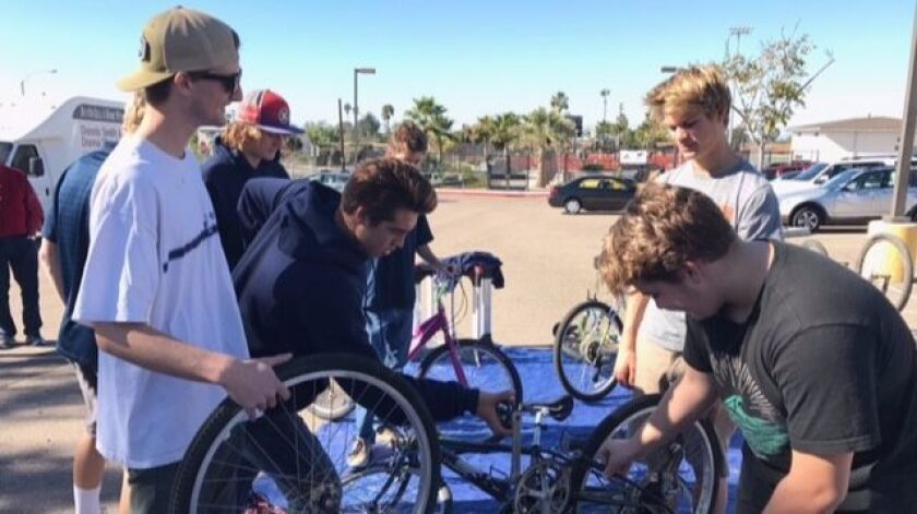 Members of the SDA boys water polo team — from left, Connor Dahl, Gavin Silberman (red hat), Matheus Gensler, Sean Gahman, Jake Holland and Jude Irons — repair bicycles donated as part of the team's Dec. 4 Bike Drive. The bikes will be given to the CRC for its Holiday Baskets.