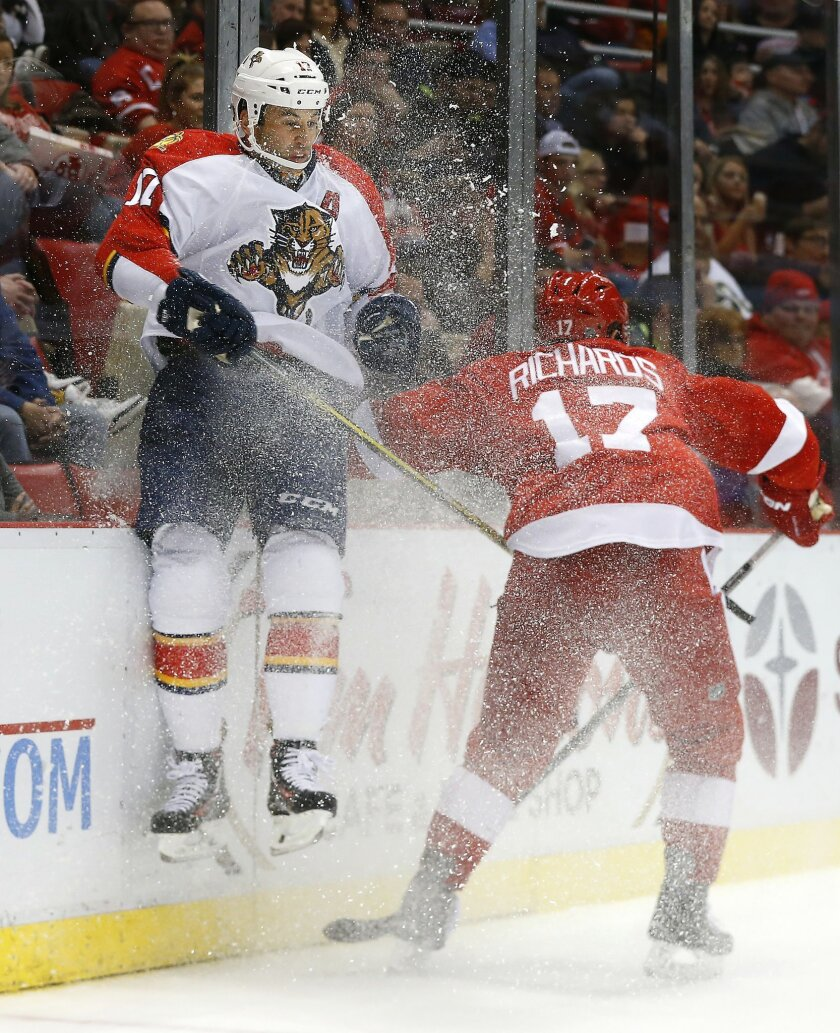 Detroit Red Wings center Brad Richards (17) checks Florida Panthers center Derek MacKenzie (17) into the boards in the second period of an NHL hockey game, Monday, Feb. 8, 2016 in Detroit. (AP Photo/Paul Sancya)
