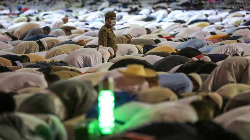 A Saudi security officer stands among Muslim worshipers as they perform prayers around the Kaaba.