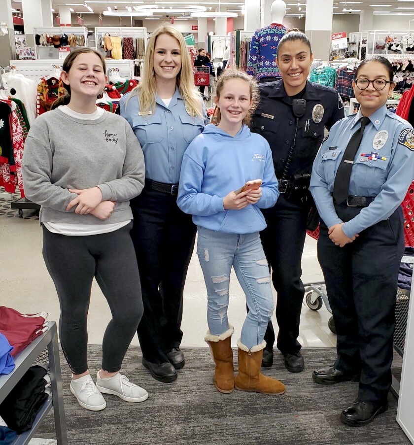 From left to ht: Carlie Farr, Police Communication Valerie Dunger, Officer Diana Valencia and Police Explorer Valeria Medina take part in the Glendale Police Officers' Assn.'s Shop with a Cop event at the Glendale Galleria Target on Friday, Dec. 6.