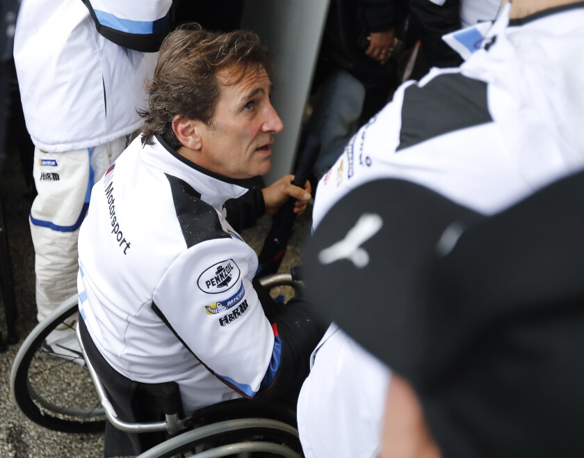 FILE - In this Sunday, Jan. 27, 2019 filer, Alex Zanardi talks with crew members in his pit stall during the IMSA 24-hour race at Daytona International Speedway, in Daytona Beach, Fla. Italian auto racing champion-turned-Paralympic gold medalist Alex Zanardi has started showing signs of interaction more than three months after he was seriously injured in a handbike crash. Zanardi had spent most of that time in intensive care after crashing into an oncoming truck during a relay event near the Tuscan town of Pienza on June 19. (AP Photo/Terry Renna, File)
