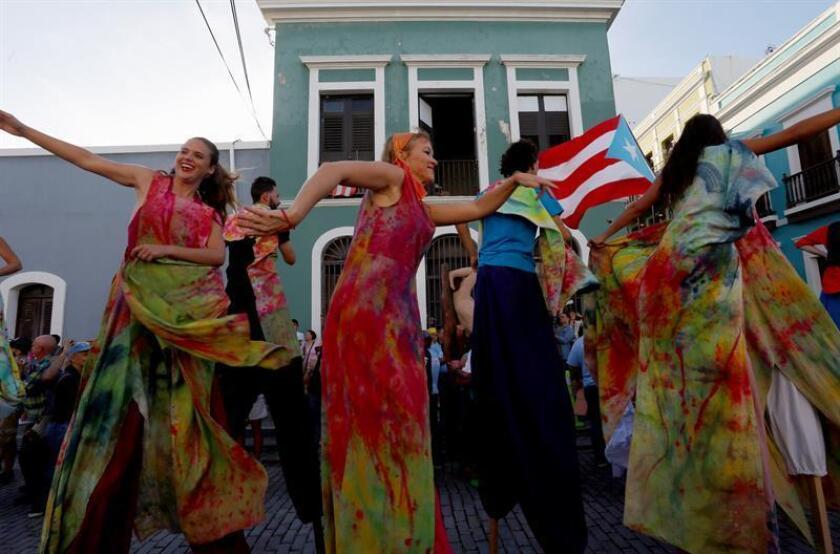 Un grupo de asistentes en zancos desfila durante la inaguración de las Fiestas de la Calle San Sebastián, en San Juan (Puerto Rico). EFE/Archivo