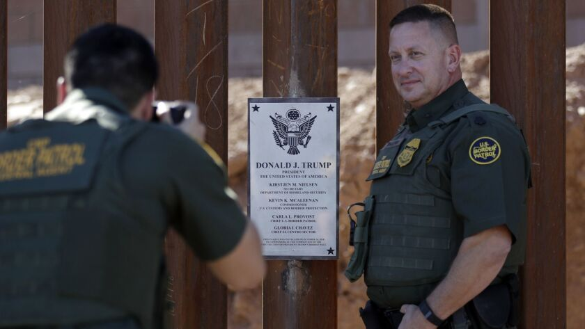 FILE - In this Oct. 26, 2018, file photo, Border Patrol agent Michael Sullivan, right, poses for a p