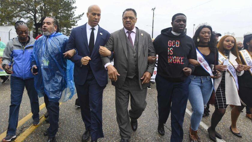 U.S. Sen. Cory Booker, D-N.J., third from left, and the Rev. Jesse Jackson march to cross the Edmund