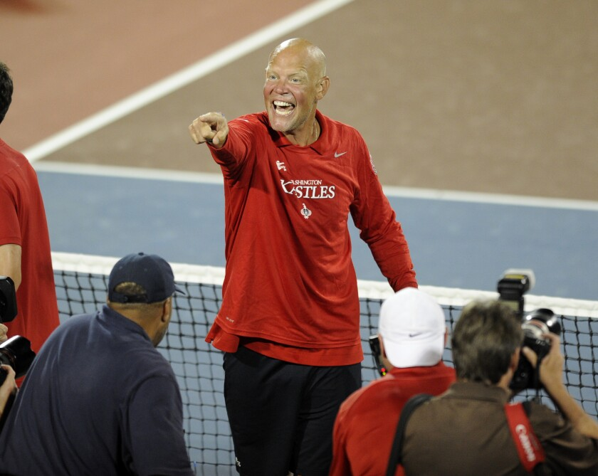 A man standing on a tennis court smiles and points to another person.