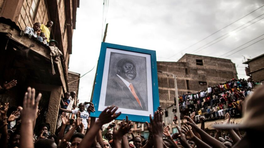 A portrait of embattled Kenyan opposition leader Raila Odinga is carried by a crowd waiting for his arrival in Mathare, a slum district of the capital, Nairobi.