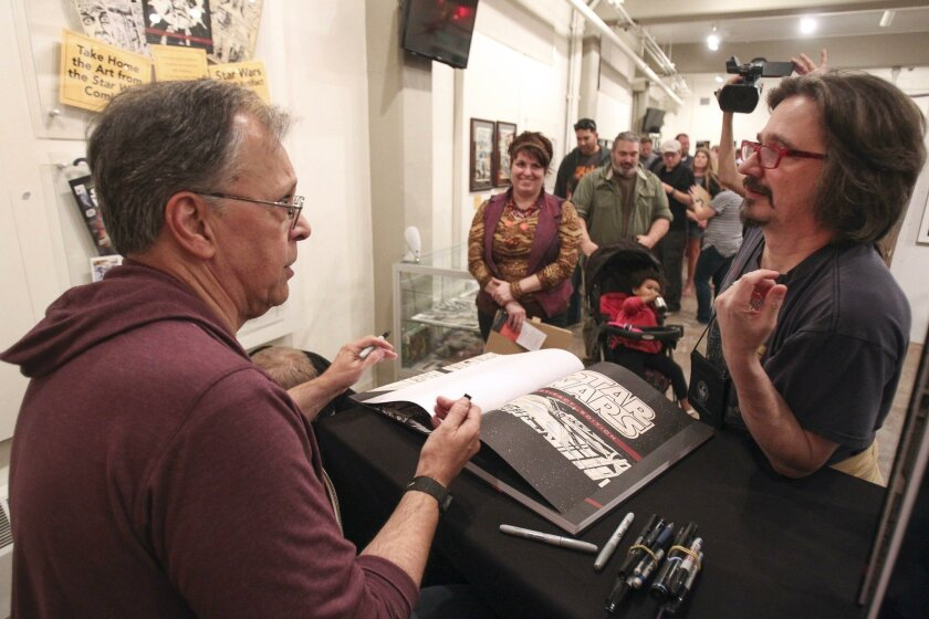 """Russell Marcontell, right, gets his book autographed by Star Wars comic artist Howard Chaykin during the """"The Art of Star Wars"""" exhibit opening."""
