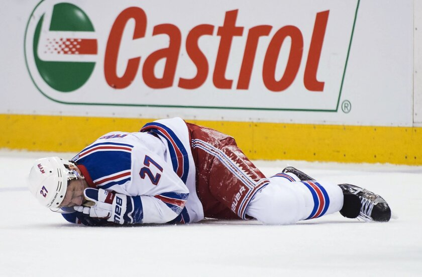 New York Rangers defenseman Ryan McDonagh (27) lies injured on the ice after taking a hit to the head from Toronto Maple Leafs center Leo Komarov during the first period of an NHL hockey game Thursday, Feb. 18, 2016, in Toronto. (Nathan Denette/The Canadian Press. via AP)