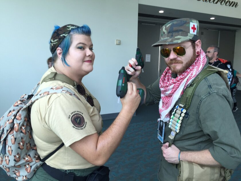"""Cosplay repair """"heroes"""" Caitlin Brown, 28, and Todd Kimmell, 31, make the rounds at San Diego's Comic-Con as visitors hail them for some quick costume repairs."""