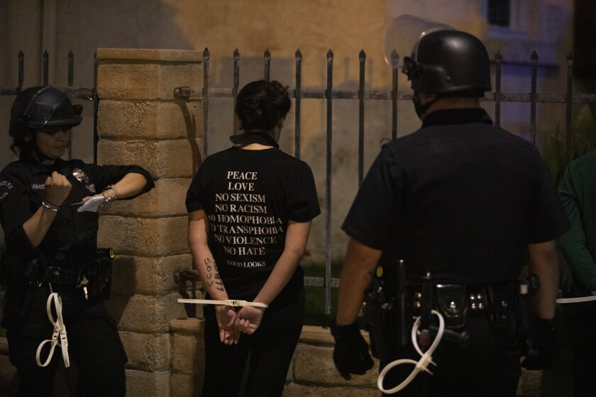 Police in Los Angeles put a protester in plastic handcuffs for curfew violation after a day of peaceful protest