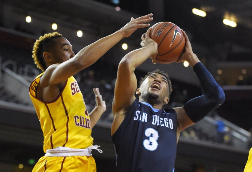 USD freshman guard Olin Carter III, right, shoots as Southern California guard Jordan McLaughlin defends during the first half of USC's 83-45 victory two weeks ago in Los Angeles. (AP Photo/Mark J. Terrill)