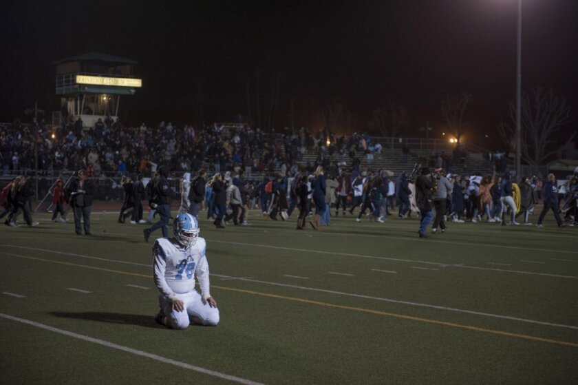 Corona del Mar's Connor Reid kneels on the field as Sierra Canyon spectators rush the field after Sierra Canyon won Friday's CIF Southern Section Division 4 championship game in double overtime at Granada Hills High School.