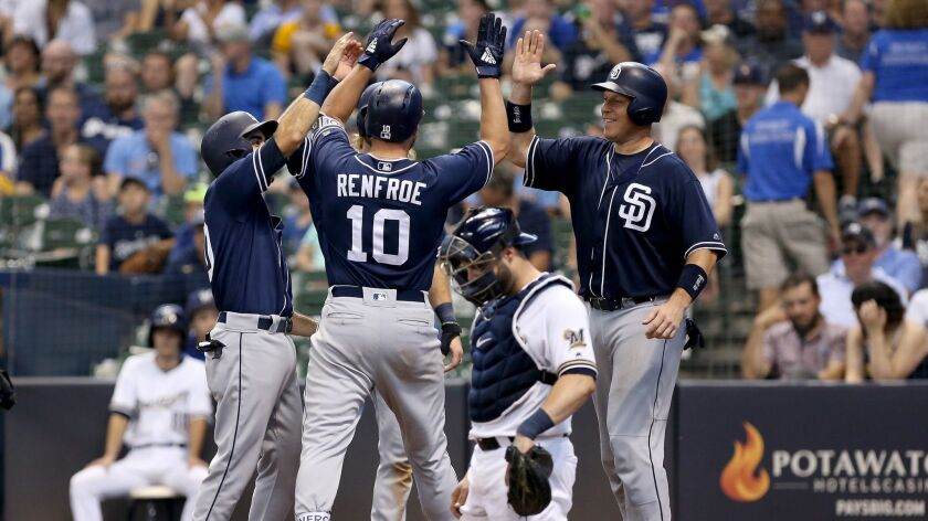Hunter Renfroe of the San Diego Padres celebrates with teammates past Manny Pina #9 of the Milwaukee Brewers after hitting a grand slam in the ninth inning at Miller Park on Thursday.