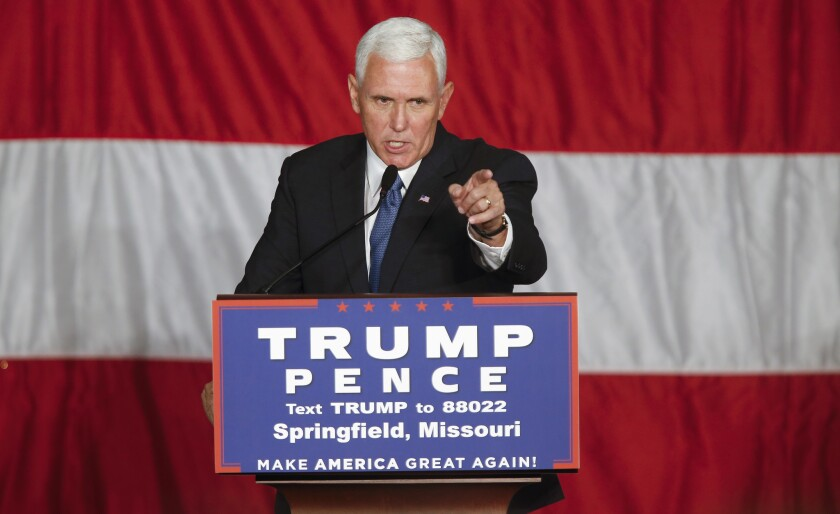 Former Vice President Mike Pence, at a campaign-stop podium, points at the crowd.