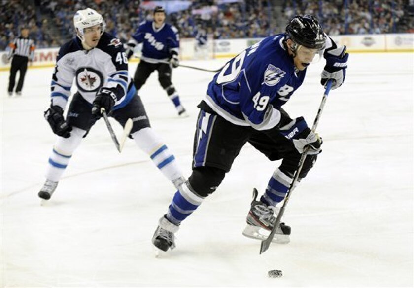 Tampa Bay Lightning right wing J.T. Brown, right, controls the puck ahead of Winnipeg Jets right wing Spencer Machacek during the second period of an NHL hockey game on Saturday, March 31, 2012, in Tampa, Fla. (AP Photo/Brian Blanco)