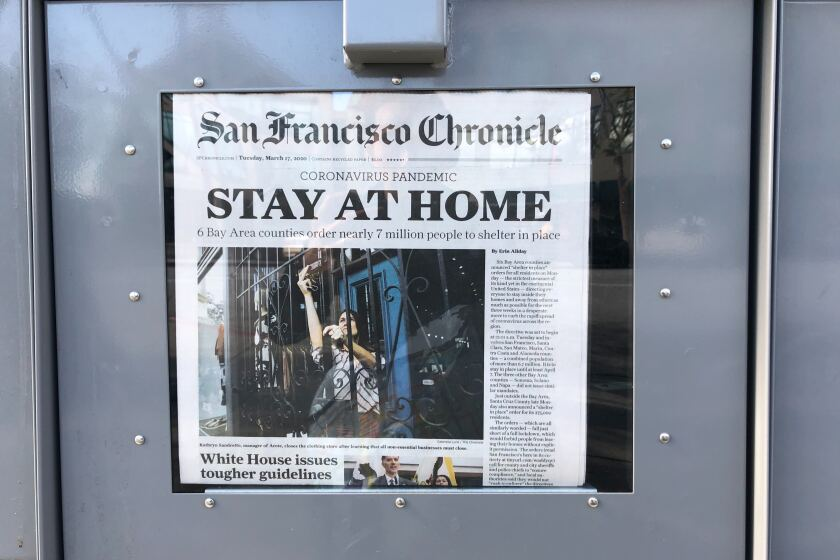 A news stand in Millbrae, Calif. displays the front page of the San Francisco Chronicle on Tuesday, March 17, 2020.