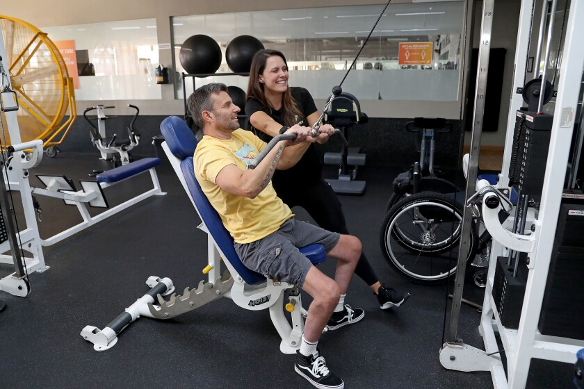 Personal trainer Ashley Griswold, top, helps start paraplegic Paul Ferguson off on his workout.