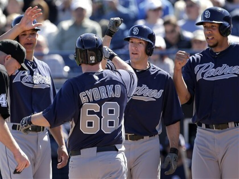 San Diego Padres' Jedd Gyorko (68) celebrates with teammates Will Venable, left, Chris Denorfia, center, and Kyle Blanks after he hit a grand slam during an exhibition spring training baseball game against the Seattle Mariners Friday, Feb. 22, 2013, in Peoria, Ariz. (AP Photo/Charlie Riedel)