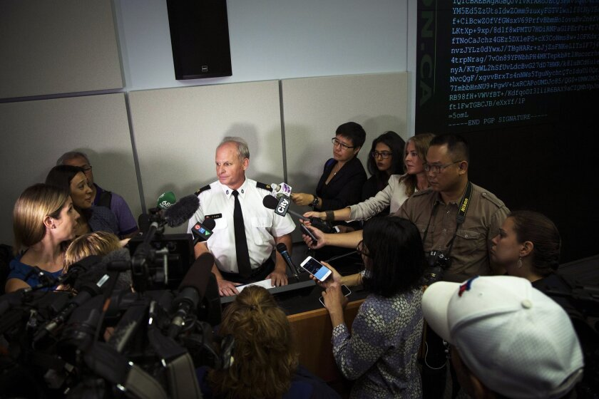 Toronto Police Services Superintendent Bryce Evans, center, speaks to the media regarding the investigation into the AshleyMadison.com breach during a press conference in Toronto on Monday, August 24, 2015. The hack of the cheating website Ashley Madison has triggered extortion crimes and led to two unconfirmed reports of suicides, Canadian police said Monday. The company behind Ashley Madison is offering a $500,000 Canadian (US $378,000) reward for information leading to the arrest of members of a group that hacked the site. (Melissa Renwick/Toronto Star, The Canadian Press via AP)