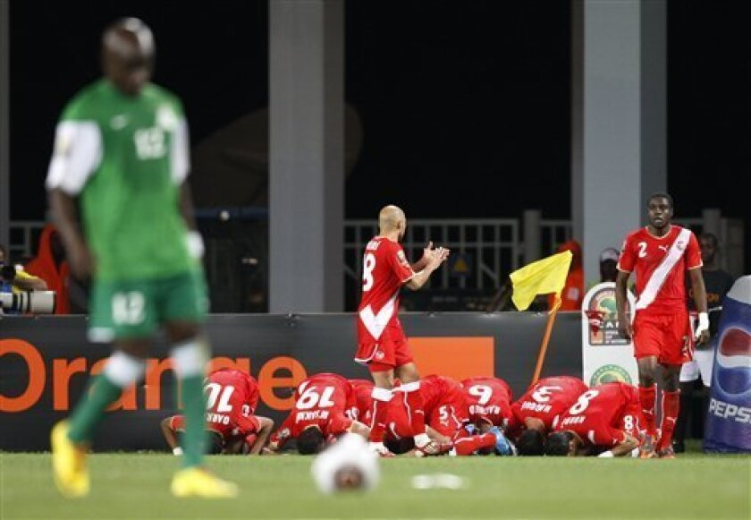Tunisia players kneel in prayer as they celebrate a goal by Zouhaier Dhaouadhi in their African Cup of Nations Group D soccer match against Zambia at Tundavala Stadium in Lubango, Angola Wednesday, Jan. 13, 2010. (AP Photo/Rebecca Blackwell)